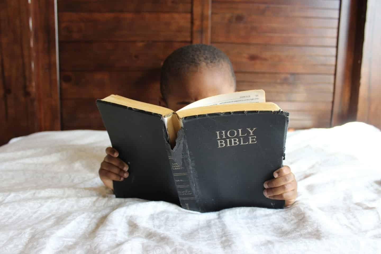 menino lendo bíblia